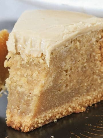 A piece of caramel mud cake with frosting on top.
