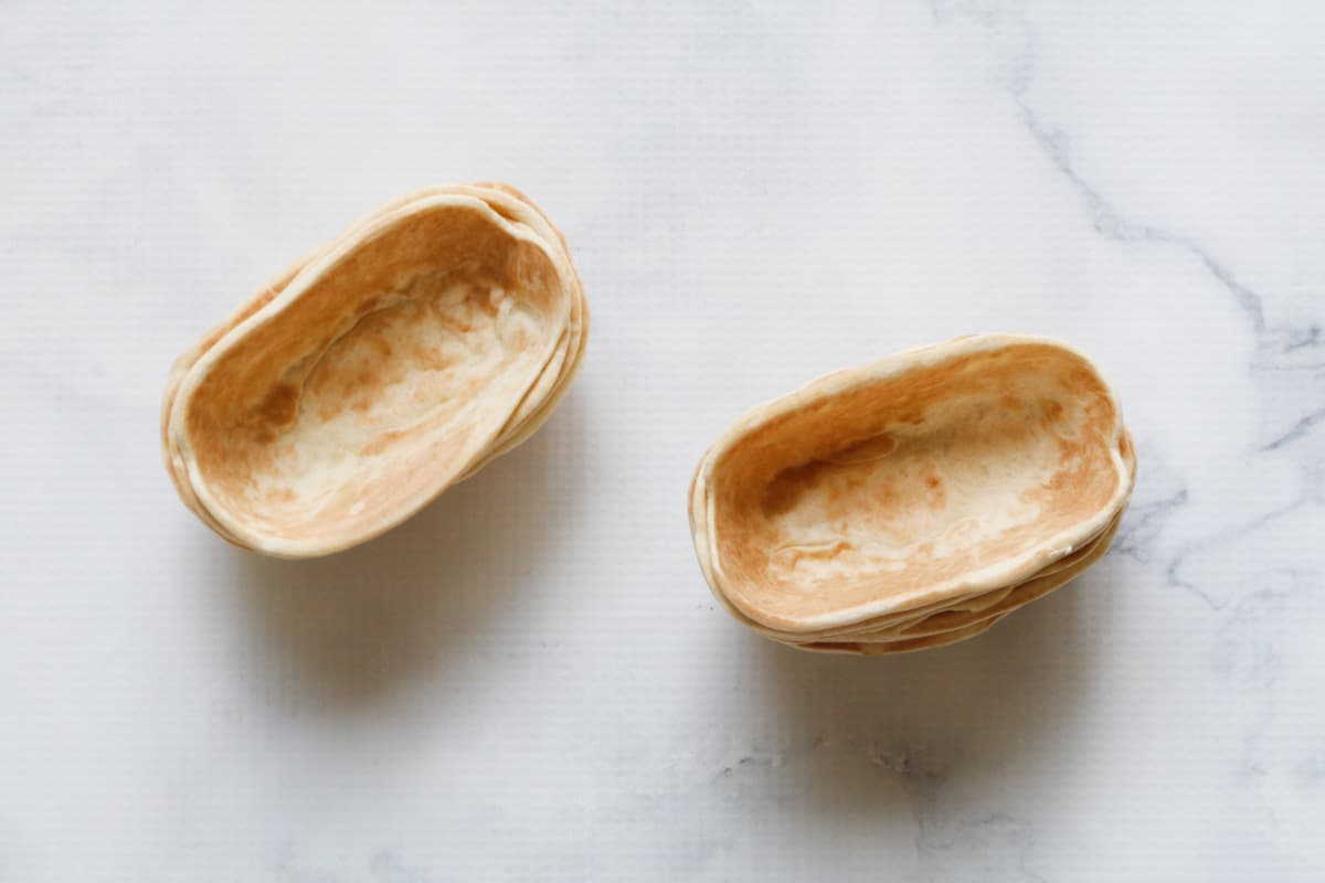Two stacks of empty tortilla shells on a marble counter