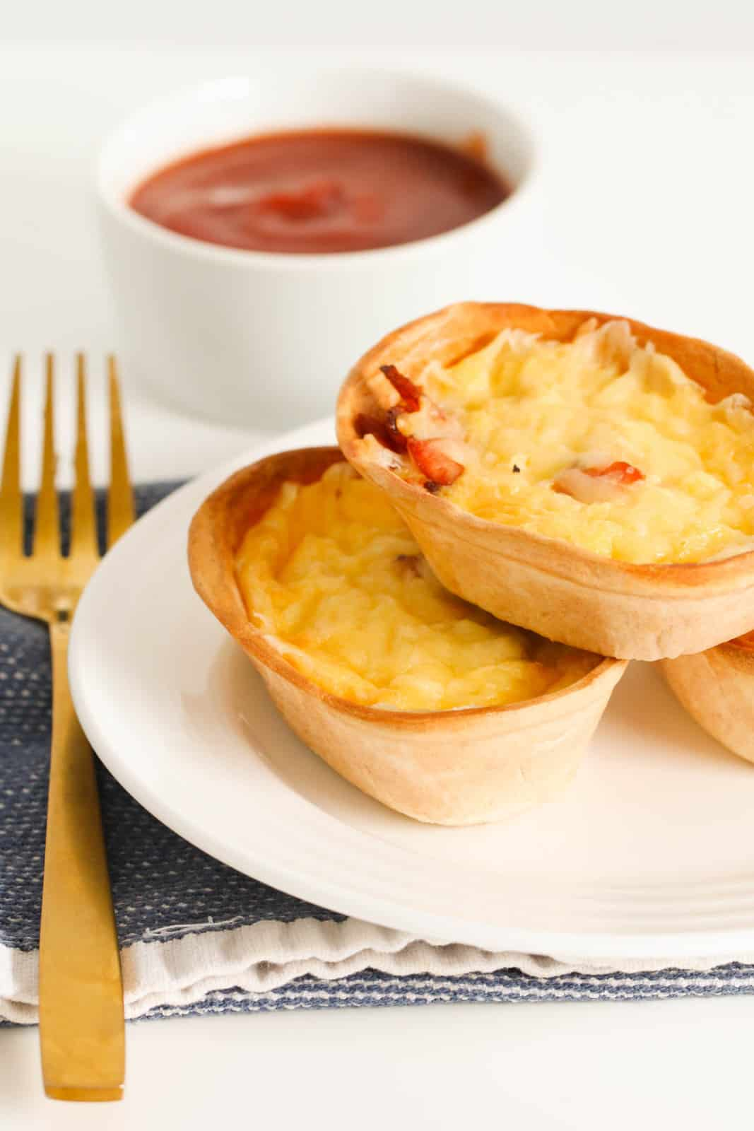 A fork beside a white plate with a stack of quiches in front of a ramekin with tomato sauce