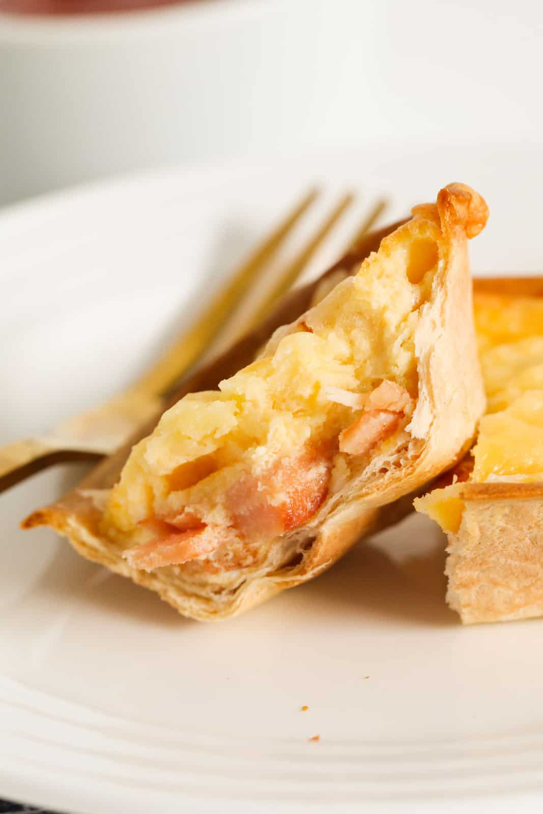 A tortilla quiche cut in half on a white plate showing the inside filling