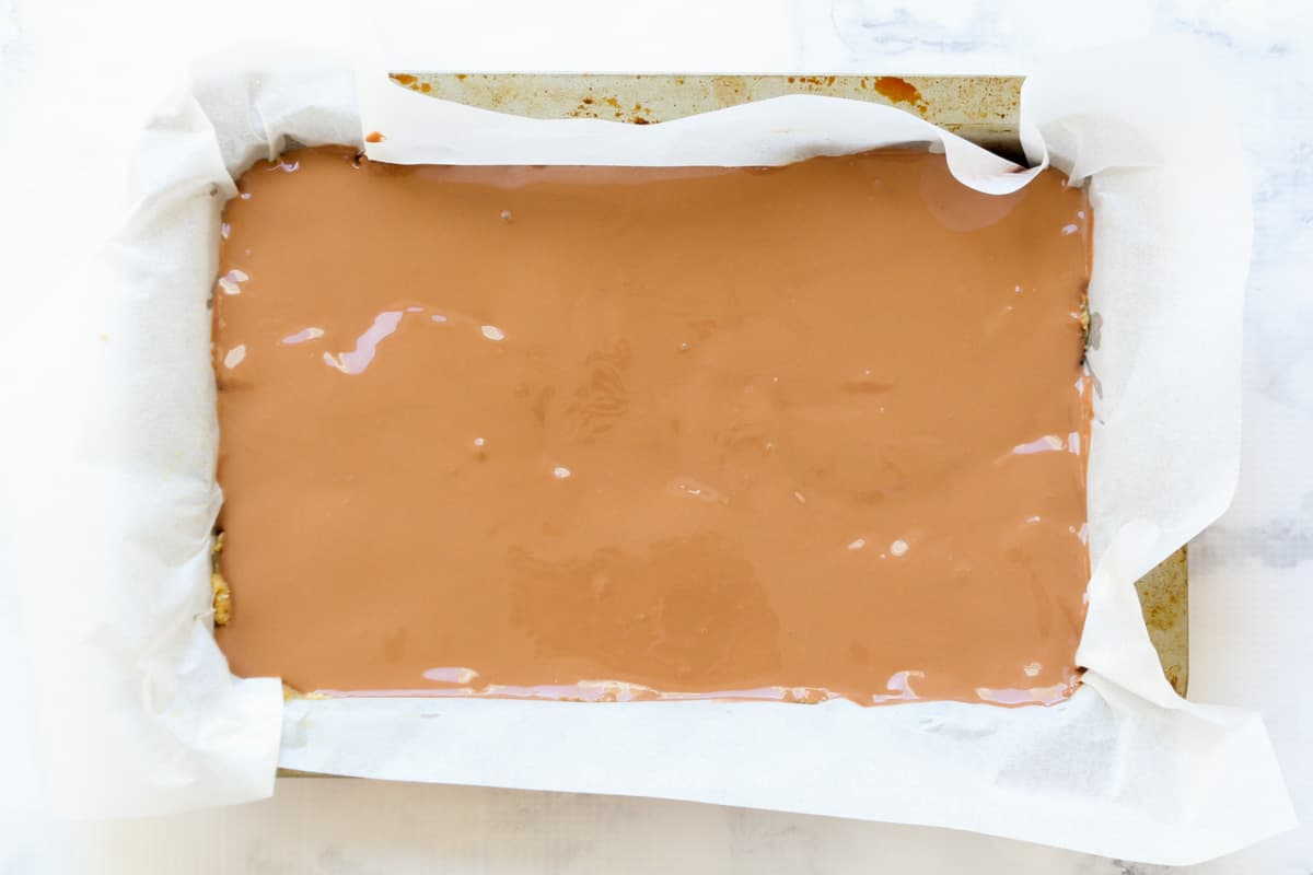 Milk chocolate spread over the top of a slice, in a paper lined slice tin.