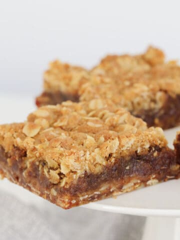 A piece of crumble slice with a date filling.