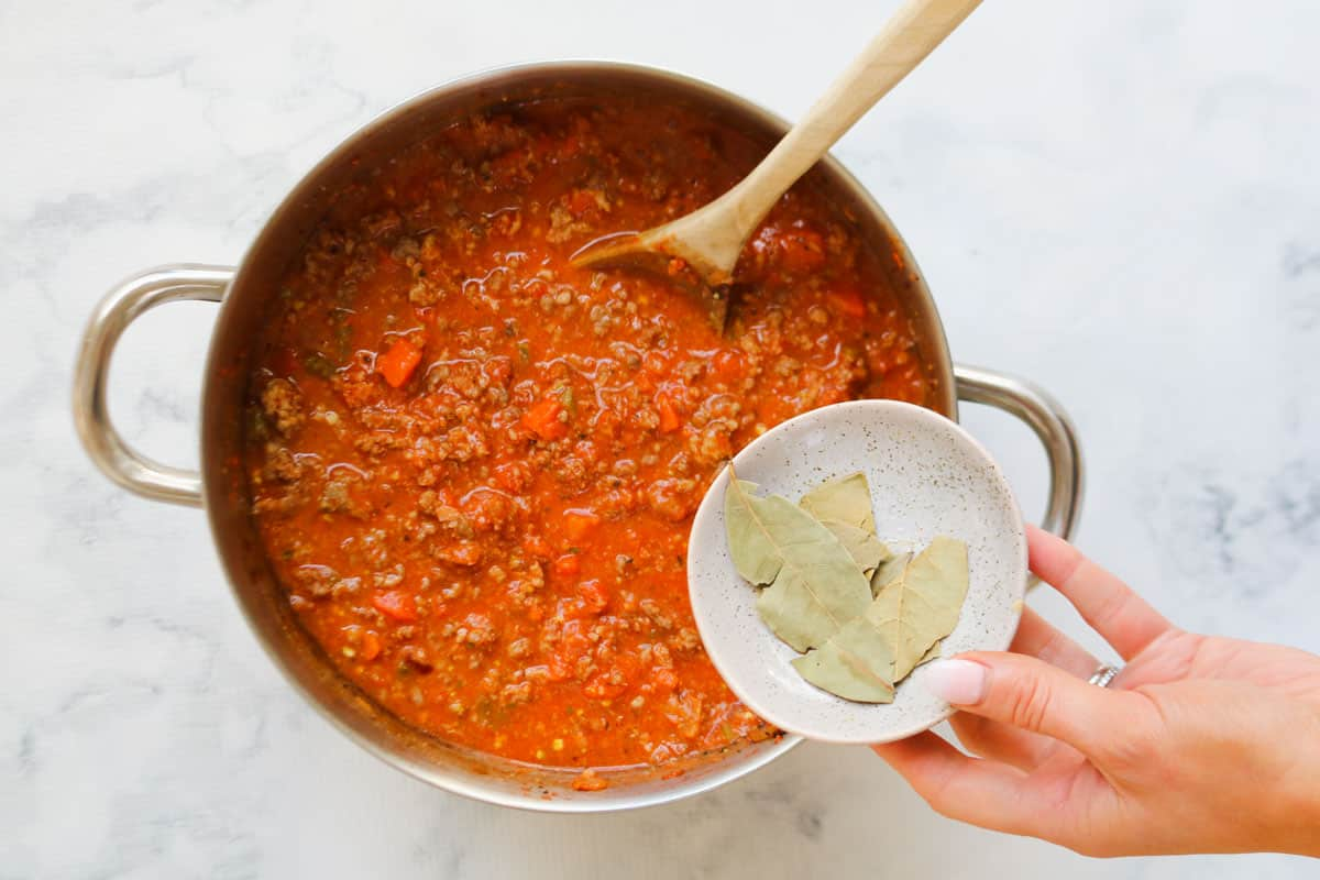 Bay leaves being added to a pot of bolognese pasta sauce.
