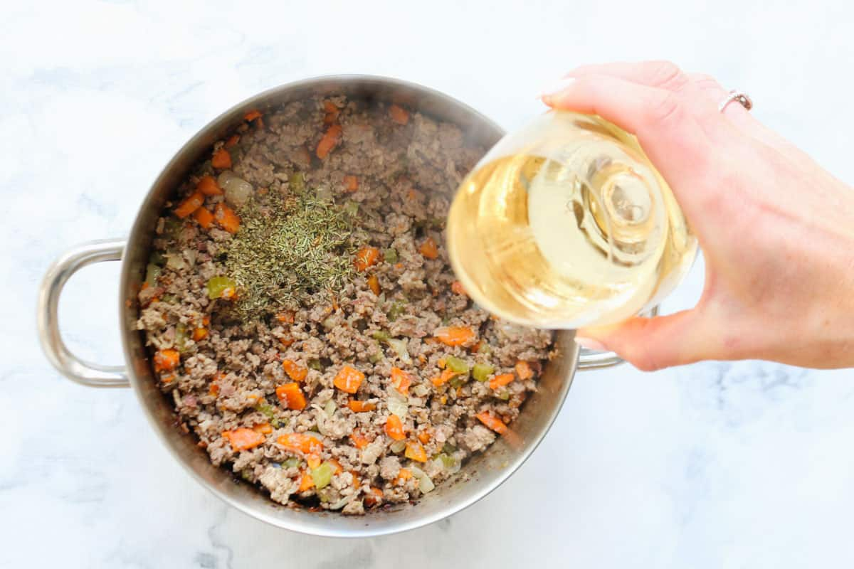 Wine and herbs being added to a meat and vegetable mixture in a pot.