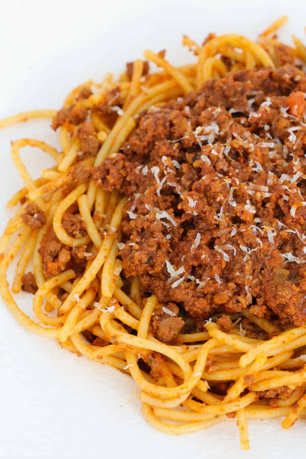 An overhead shot of a plate filled with pasta and meat sauce, with grated parmesan sprinkled over the top