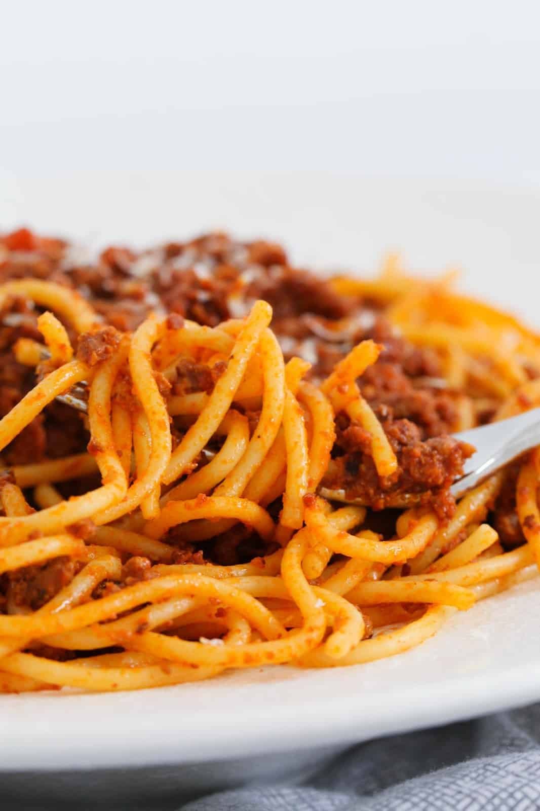 Spaghetti bolognese twirled around a fork in a bowl.
