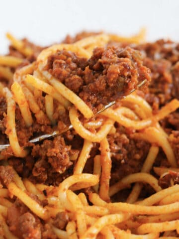A bowl of pasta coated in a meat and tomato sauce.