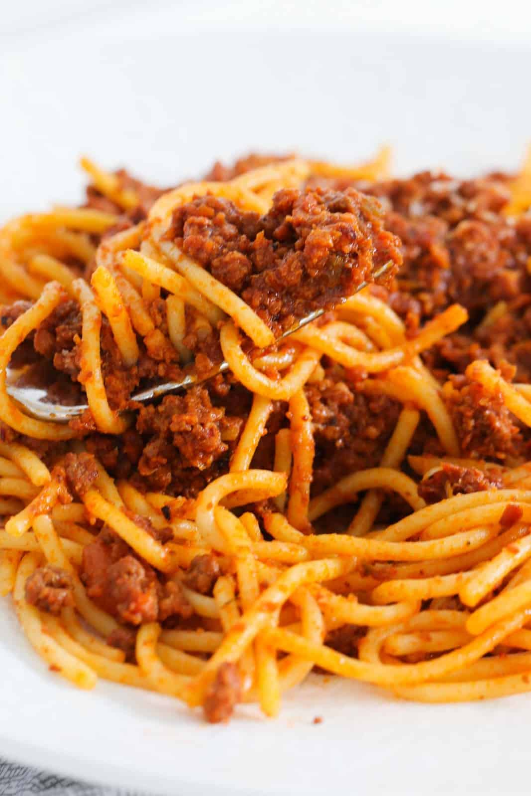 A bowl of pasta coated in a rich meat and tomato sauce.