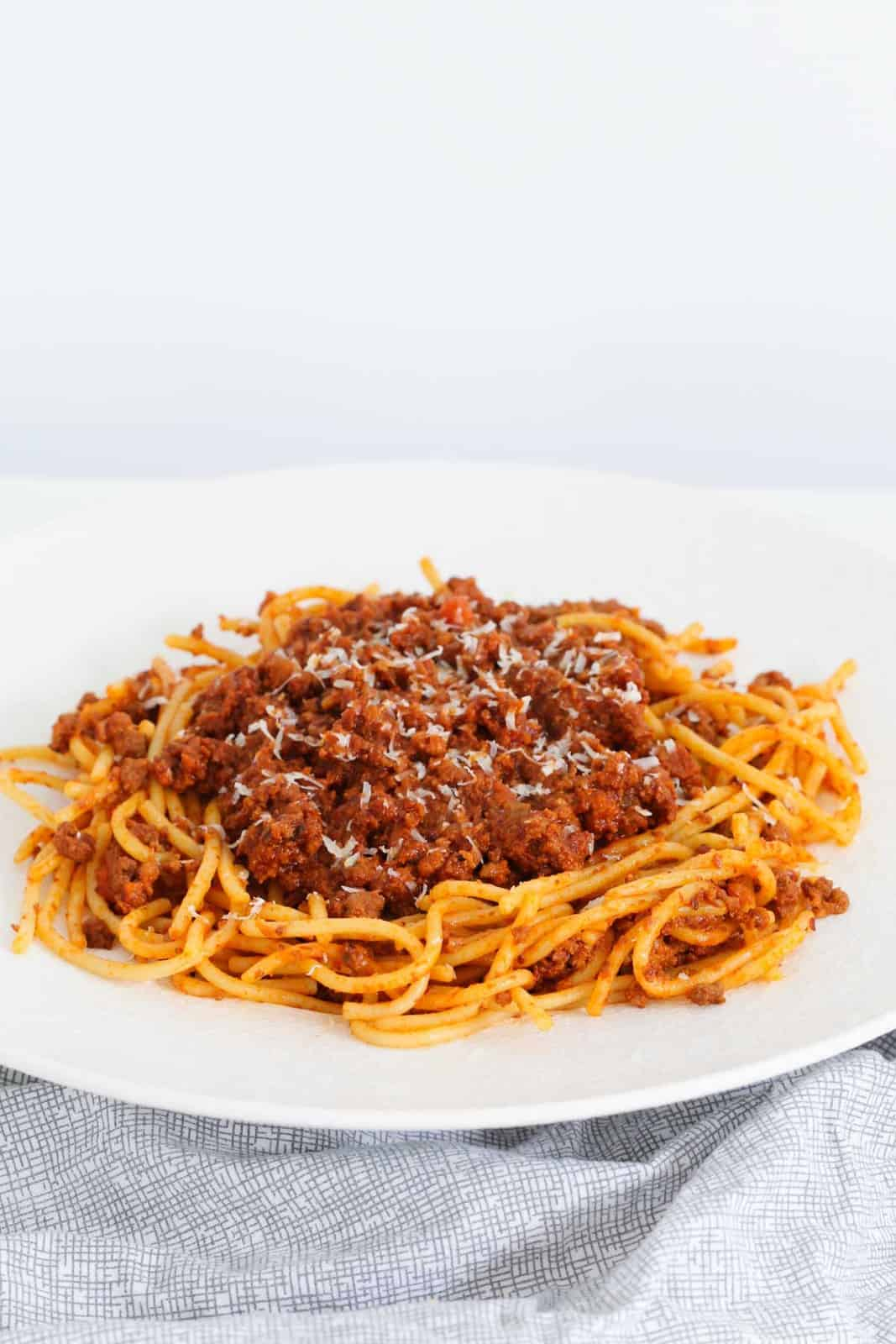 A bowl of spaghetti with minced meat sauce, sprinkled with grated parmesan