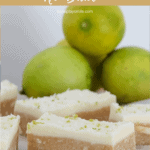 Pieces of a coconut & lime slice with white frosting, in front of fresh limes