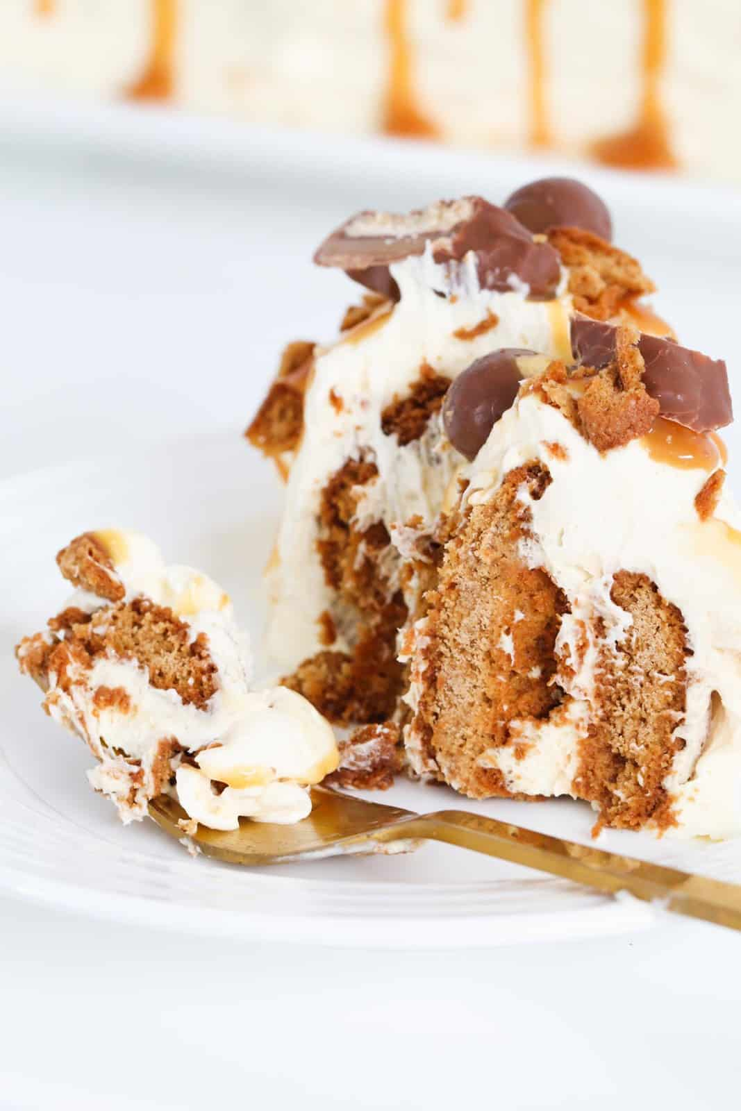 A forkful of gingernut log with whipped cream.