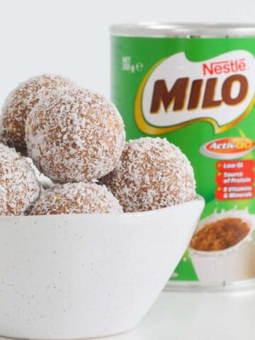 A bowl filled with malted milk and coconut balls.