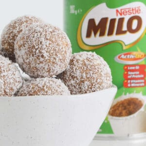 A bowl filled with coconut covered balls with a Milo tin in the background.