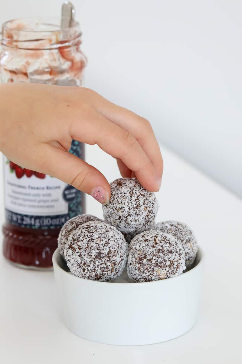 A hand reaching for a coconut 'Lamington' bliss ball in a bowl.