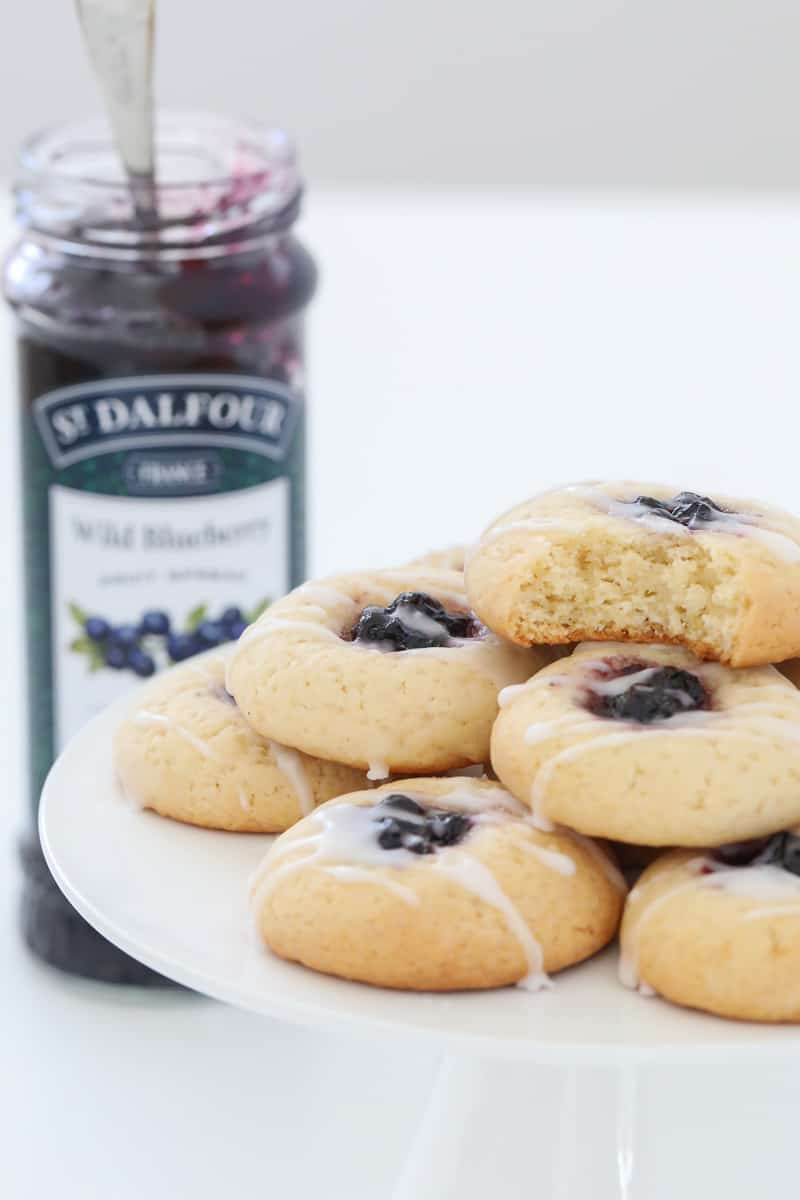 A half eaten cookie with blueberry jam and lemon drizzle, on top of a pile of more cookies.