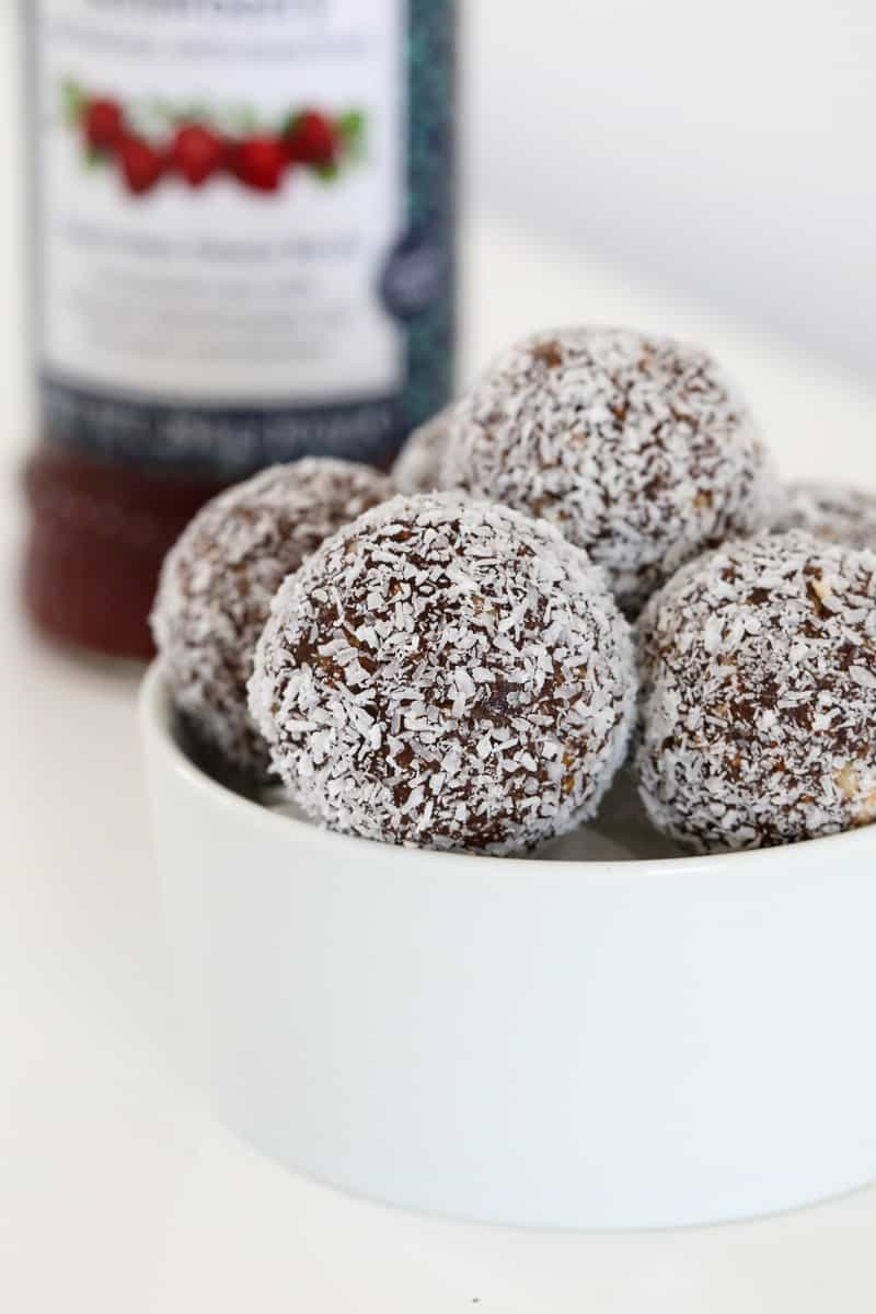 Coconut coated healthy bliss balls in a bowl.