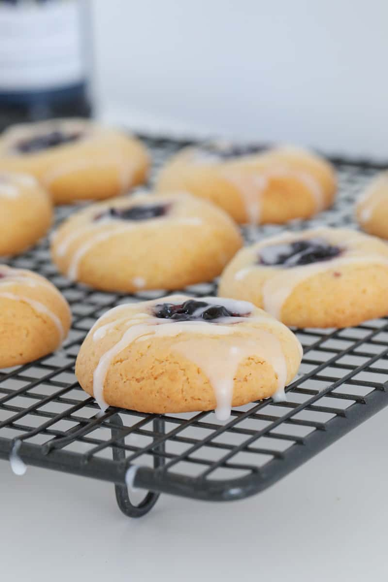 Lemon icing drizzled over golden cookies with jam in the middle, on a wire tray.