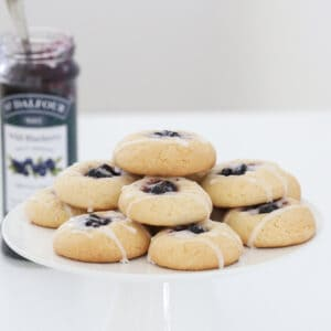 Blueberry and lemon cookies on a white cake stand.