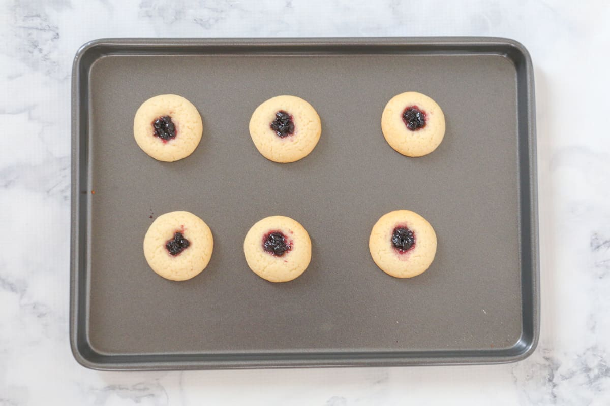 A tray of baked blueberry thumbprint cookies.