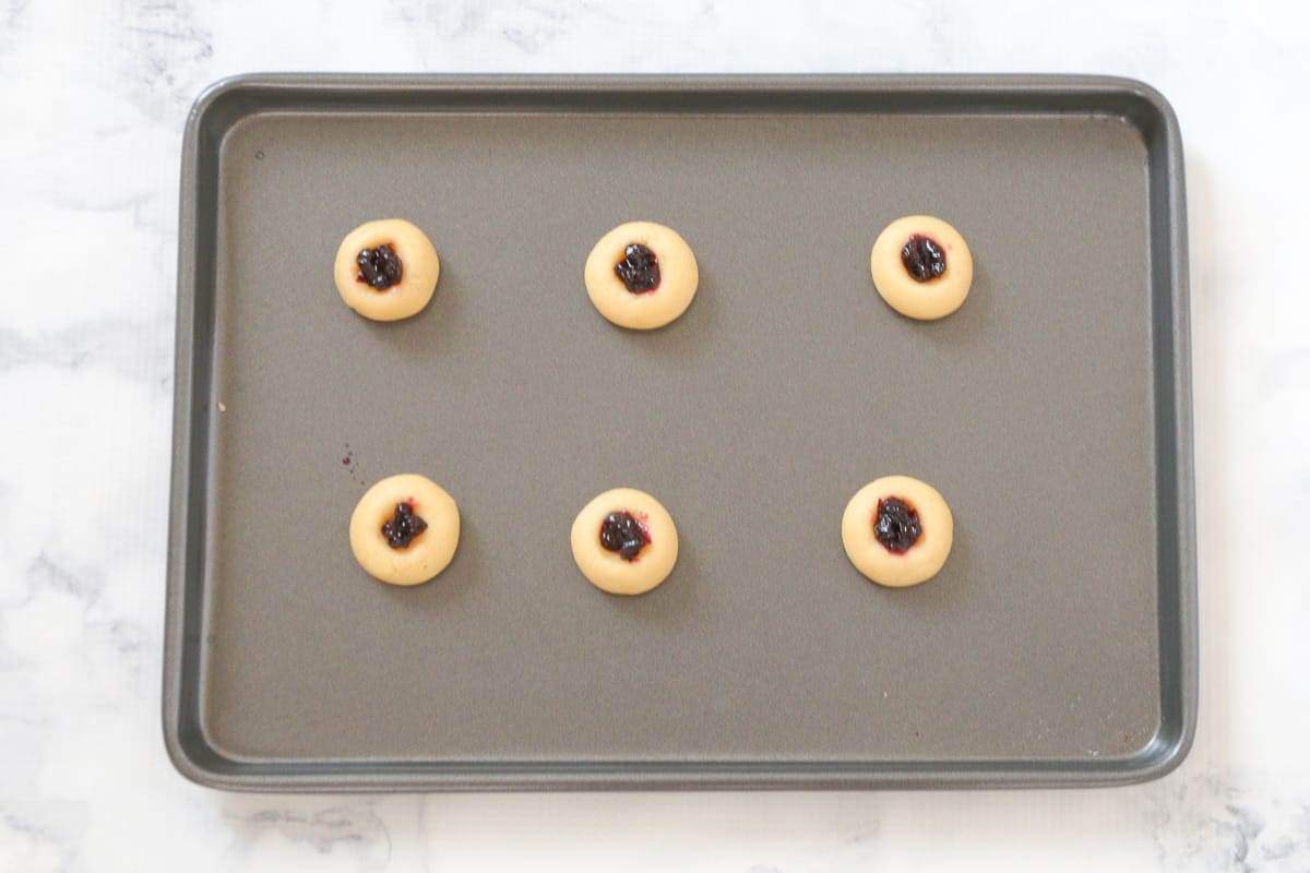 Blueberry jam in the middle of cookie dough on a tray.