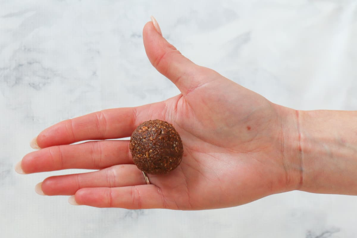 A hand holding a rolled chocolate date and almond bliss ball.