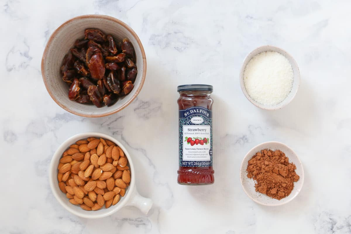 All the ingredients for chocolate, jam and coconut bliss balls.