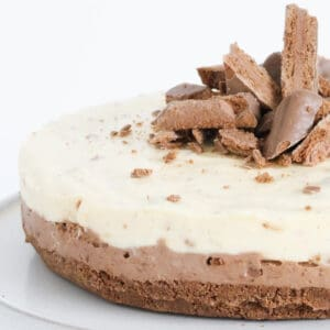 A close up view of a double layered cheesecake with chocolate biscuits on top.