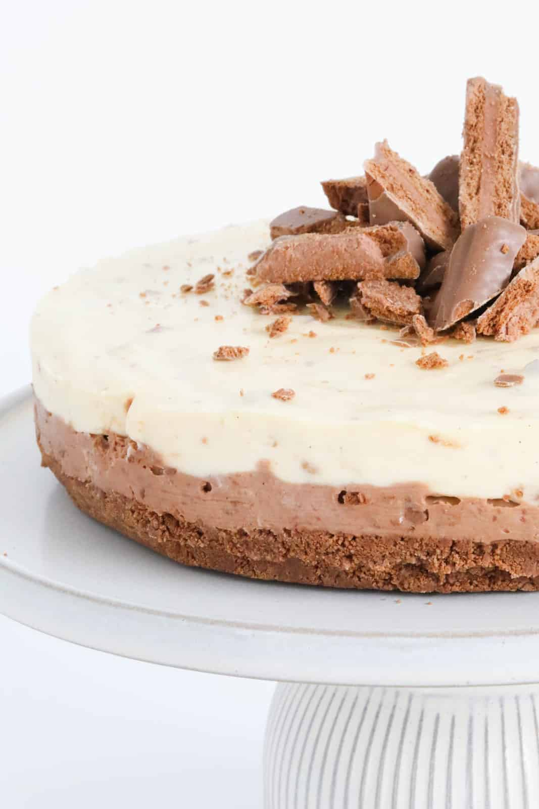 A close up view of a double layered cheesecake with chunks of chocolate biscuits on top.