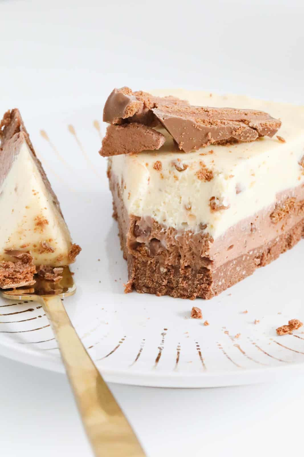A half eaten piece of white and milk chocolate cheesecake.