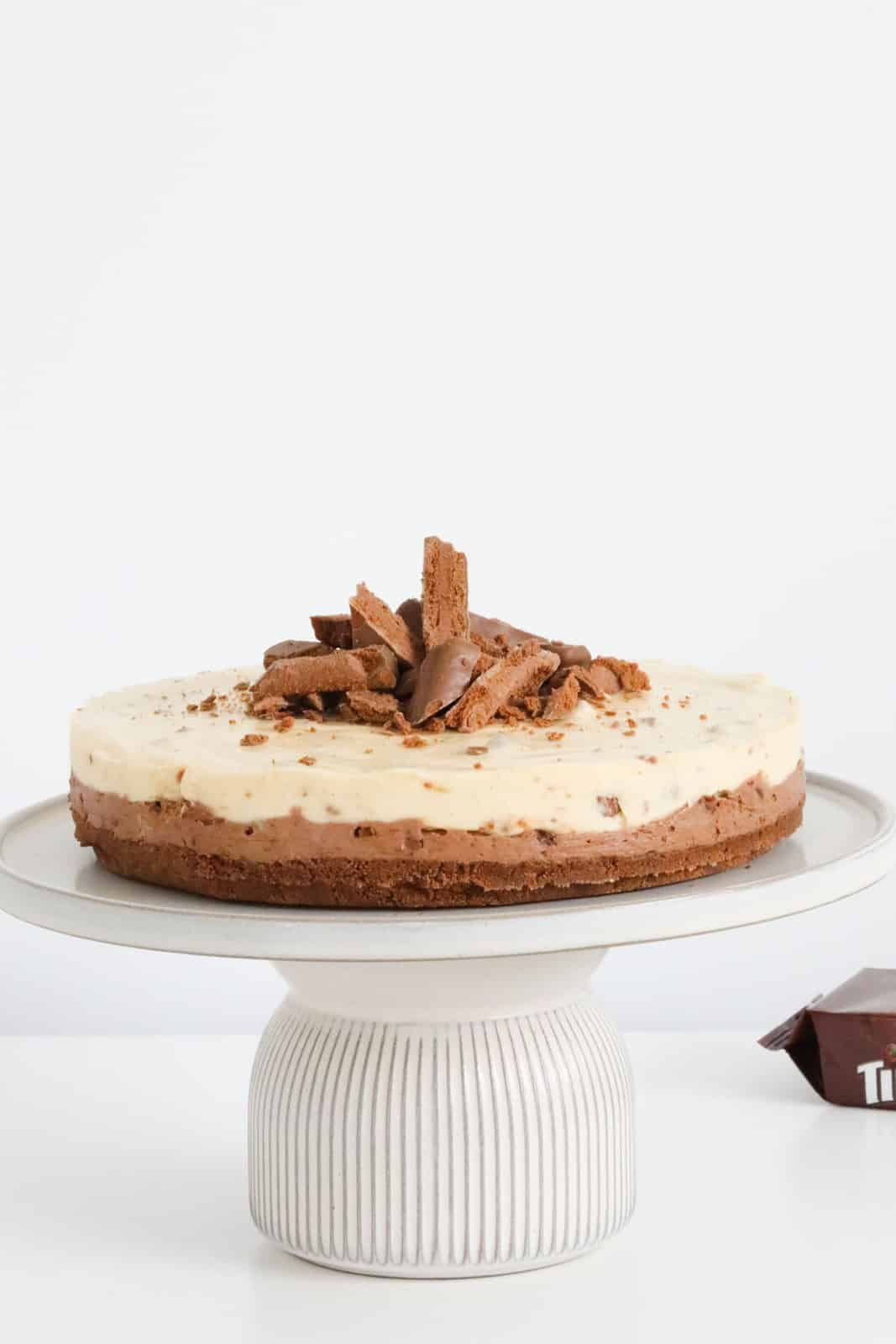 A double layered Tim Tam cheesecake on a cake stand.