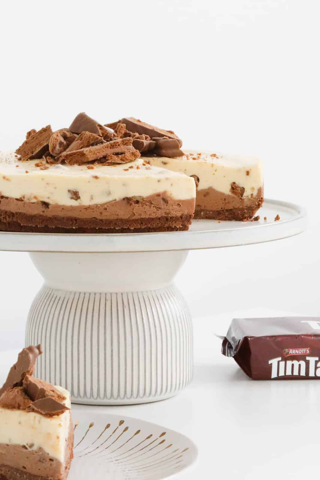 A double layered white and milk chocolate cheesecake on a cake stand, with a slice removed.