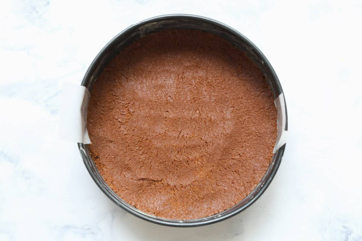 Tim Tam mixture in the base of a round lined tin.