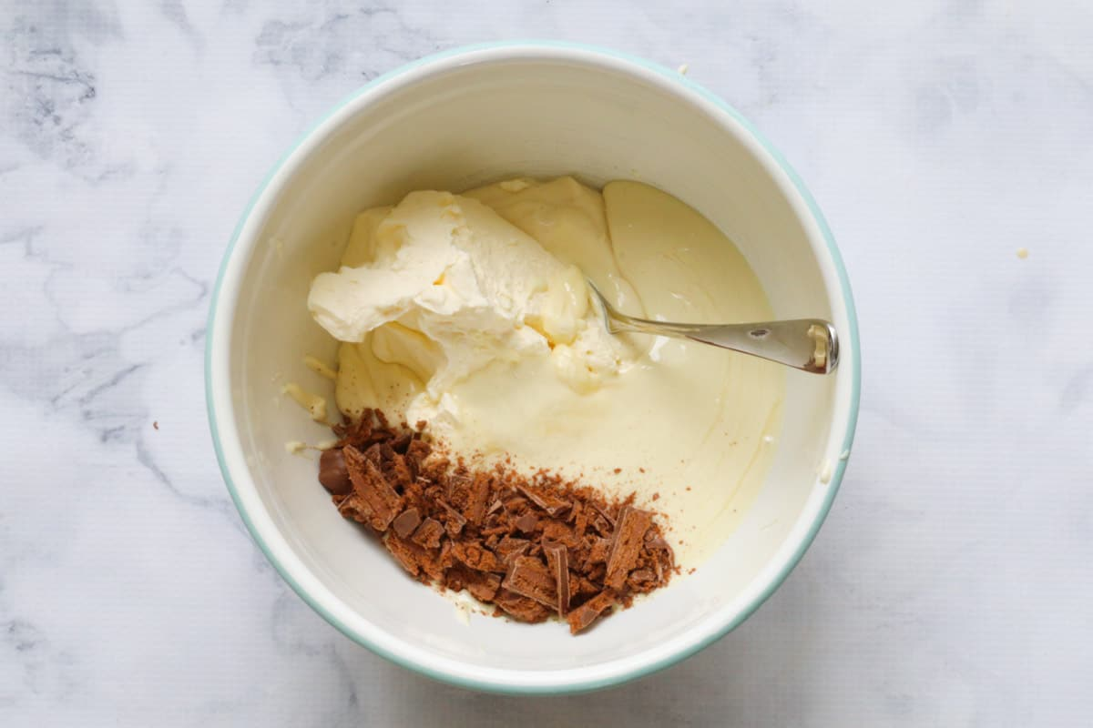 White chocolate and Tim Tam cheesecake mixture in a bowl.