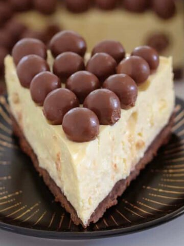 A slice of Baileys Malteser Cheesecake with Maltesers on top.