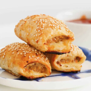 zoomed in image of three chicken sausage rolls on a blue and white plate