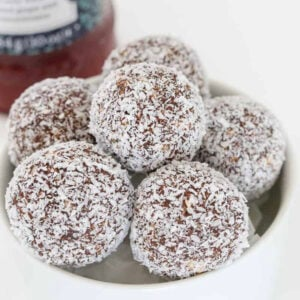 A bowl of chocolate balls coated in coconut.
